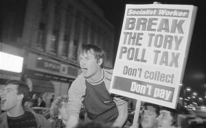 """Una manifestazione di protesta contro la Poll Tax. I cartelli esortano apertamente a boicottare il nuovo balzello della Thatcher, la  """"Robin Hood al contrario"""", che ruba ai poveri per dare ai ricchi."""