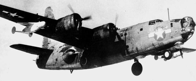 Un pattugliatore Consolidated PB4Y-2 Privateer della U.S. Navy in atterraggio su una base nel Pacifico mostra due velivoli da attacco teleguidati Bat appesi sotto le ali.