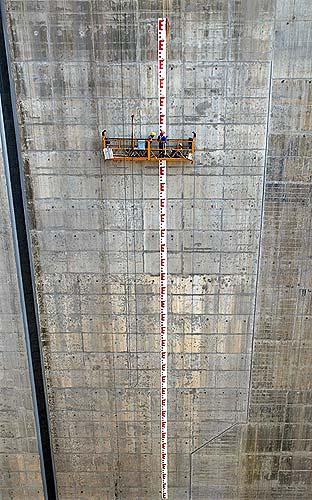 Due ingegneri cinesi ispezionano il livello dell'acqua in una delle tre dighe costruite sul fiume Yangtze.